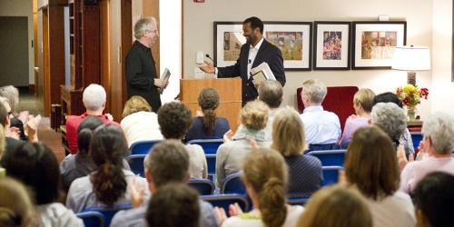 Two faculty members greeting one another at a lecture