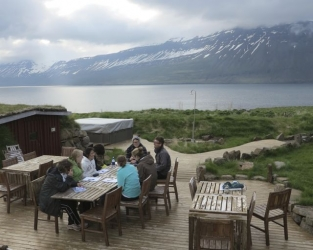 student huddle around a table with a view of a lake and mountian in the background.