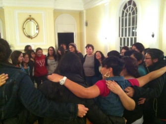 students in circle with arms around one another