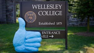 4 foot papier-mache blue thumb next to Wellesley College sign